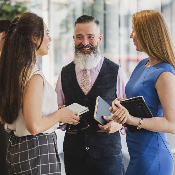 Business networking at corporate event, mature man with handlebar moustache and waistcoat smiling and listening, collaboration, diversity, individuality